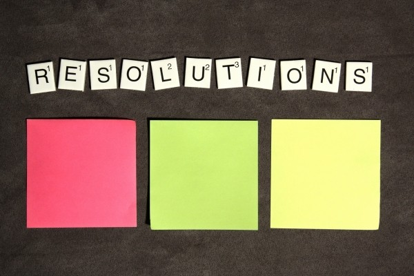 the word resolutions spelled out in Scrabble tiles above three different colored stick notes
